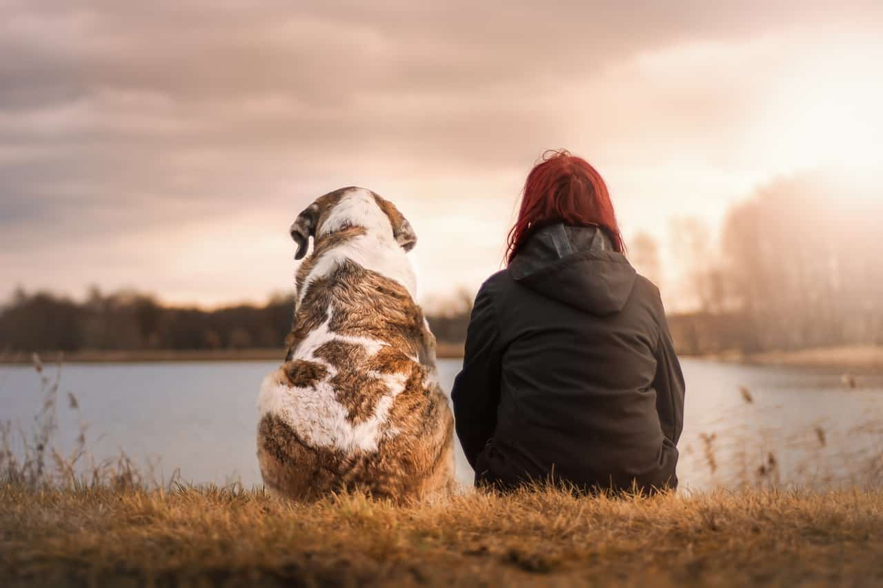 woman sitting with a dog along a river