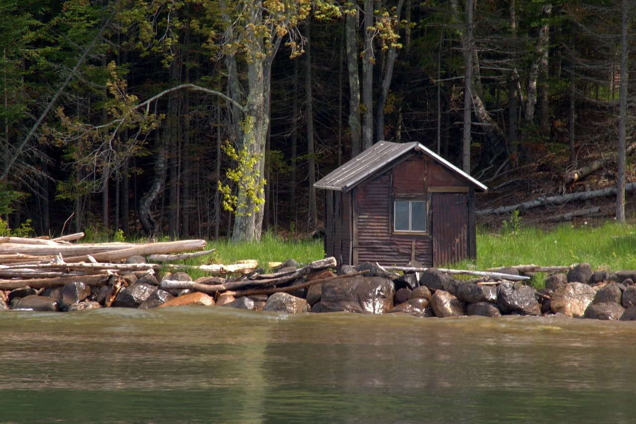 wooden cabin besides a river