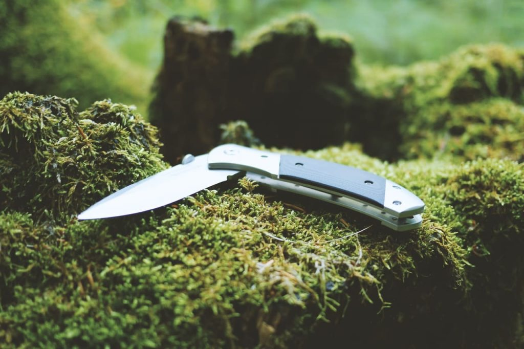 folding knife on a green grass in the wilderness