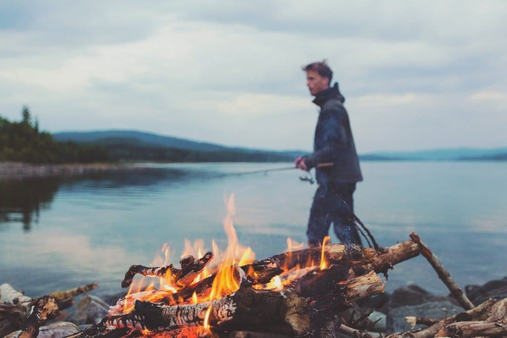 a guy camping besides a lake and a bonfire